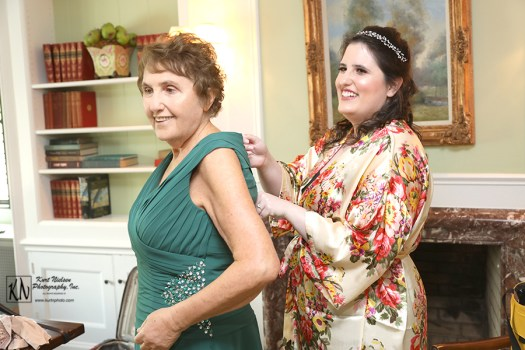 the bride helping her mother into her dress
