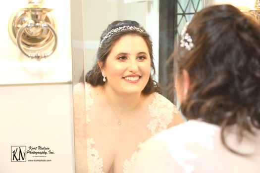 the smiling bride looking at her reflection in the mirror