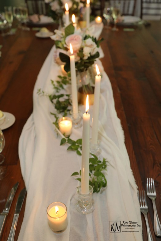 white votive and taper candles for the head table at a wedding
