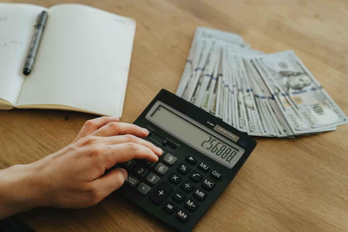 person holding black desk calculator