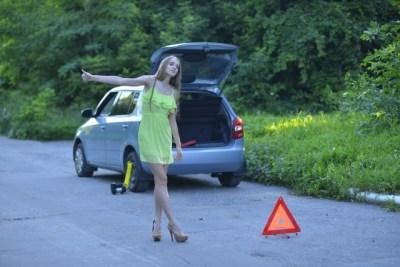 路上で止まった車で待つ女性