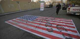 A mock US flag is laid on the ground for cars to drive on in the Iraqi capital Baghdad on January 3, 2020, following news of the killing of Iranian Revolutionary Guards top commander Qasem Soleimani in a US strike on his convoy at Baghdad international airport. (Photo by AHMAD AL-RUBAYE / AFP)