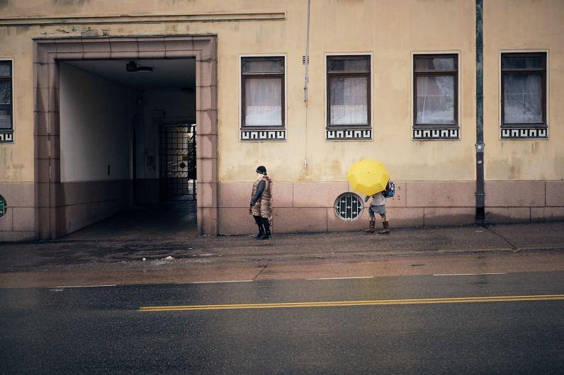 Kaksi ihmistä sateessa. Toisella keltainen sateenvarjo.