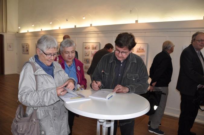 Viele Besucher nahmen die Gelegenheit wahr, sich ihre erworbenen Bücher vom Künstler signieren zu lassen (Foto:Mast)