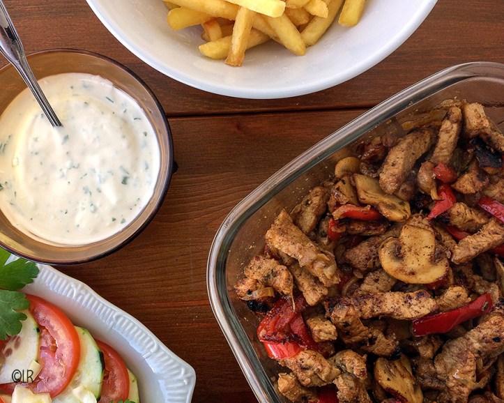 Schaal shoarmavlees met champignons en paprika met een salade, romige knoflooksaus en frietjes