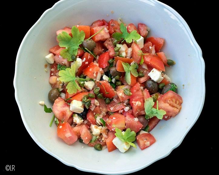 Schaal met heerlijke sappige tomaten, feta, olijven, kappertjes, ui en knoflook overgoten met rijke olijfolie.