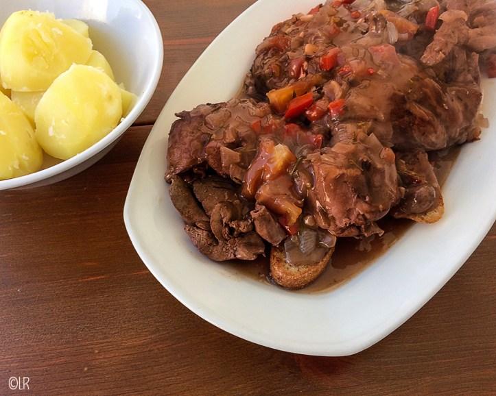 Schotel met konijndelen overgoten met de jagersaus geserveerd naast een schaaltje gekookte aardappelen.
