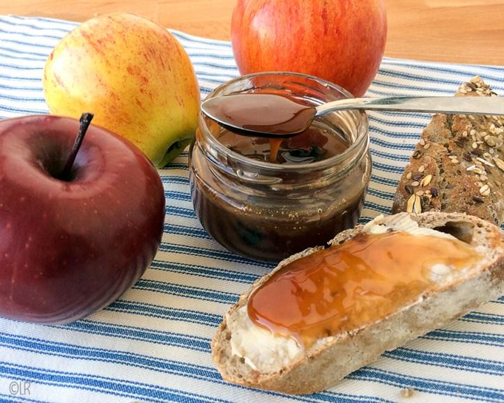Temidden van wat appels staat een potje met licht vloeibare appelstroop die van de lepel loopt. Er naast een snee volkorenbrood met pitjes besmeerd met roomboter en appelstroop
