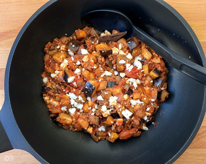 Wok met op de traditionele moussaka geïnspireerde schotel van aubergines, tomaten en gehakt.