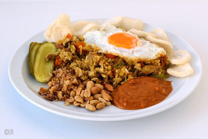 Een maaltijd op een bord: nasi goreng met kip, een gebakken ei erop en eromheen pindasaus, pinda's, gefruite uitjes, zoetzuur en kroepoek.