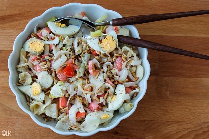 Schaal met een heerlijke maaltijdsalade van pasta, witlof, gerookte zalm en ei.