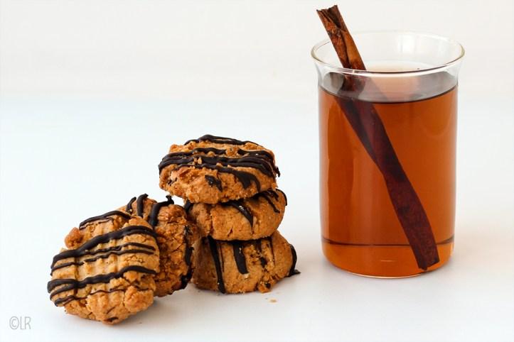 Glaasje kaneel thee met 5 koekjes.
