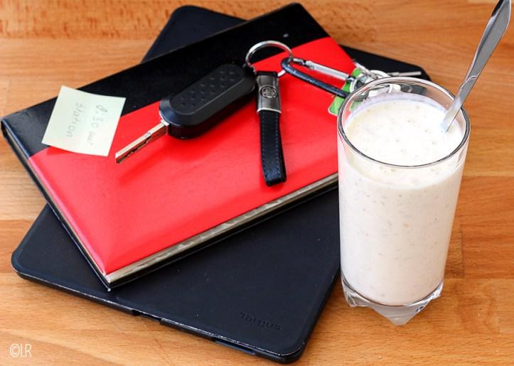 Een notebook, agenda en sleutels naast een glas drinkontbijt om de dag te beginnen.