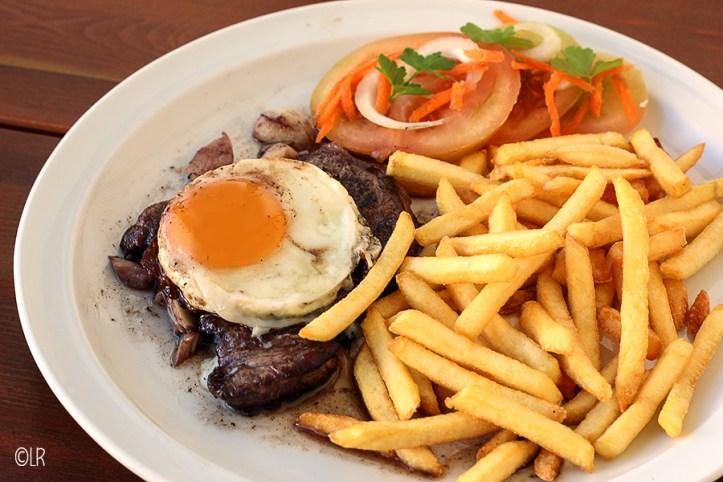 Bord met een mooi gebakken biefstuk en een gebakken ei er bovenop. Geserveerd met friet en een eenvoudige tomatensalade.