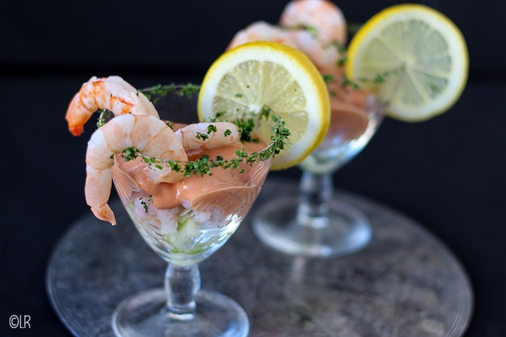 2 cocktails met garnalen, komkommer en langoustines gedecoreerd met gehakte peterselie en een schijfje citroen.