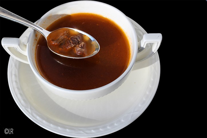 Kopje ossenstaartsoep met erboven een lepel gevuld met soep en soepvlees.