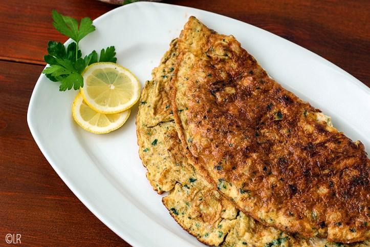 Schaal met een aan beide zijden bruin gebakken omelet met garnalen. Ernaast 2 schijfjes citroen en wat platte peterselie.