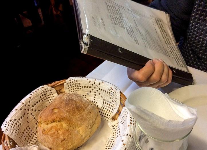 Iemand leest een vaak handgeschreven menukaart in een klein restaurant in Portugal