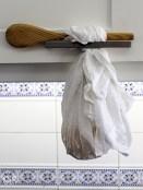 Een kaasdoek gevuld met kwark die met een houten lepel is opgehangen aan het handvat van een keukenkastje.