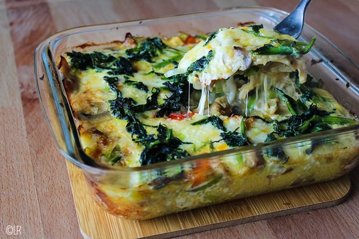 Ovenschotel waaruit met een vork een schepje wordt genomen, je kunt goed de gesmolten kaas zien.