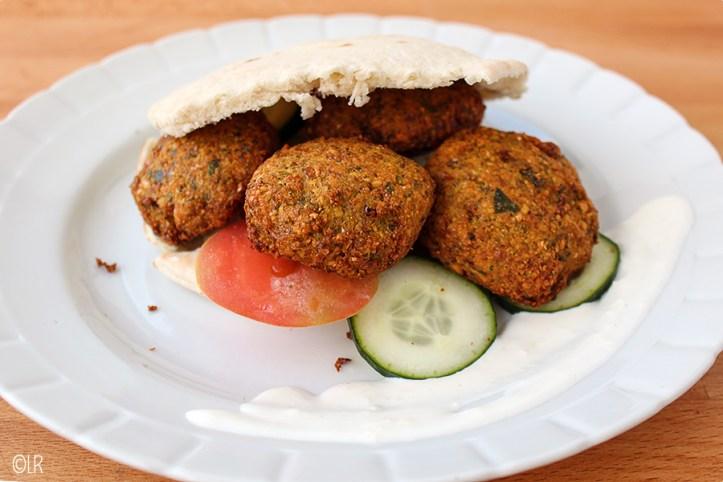 Pitabroodje met enkele falafel balletjes en wat tomaat en komkommer geserveerd met wat knoflooksaus.