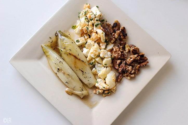 Gesmoorde witlof met ei, feta en walnoten. Mix op het bord door elkaar voor een heerlijke salade.