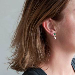 Person wearring hive earrings made of sterling silver and pink and green enamel paint featuring cascading butterflies.