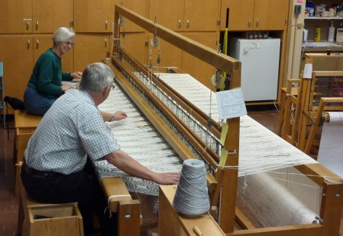 Members weave a coverlet together on the 120 inch loom at the Guild studio.