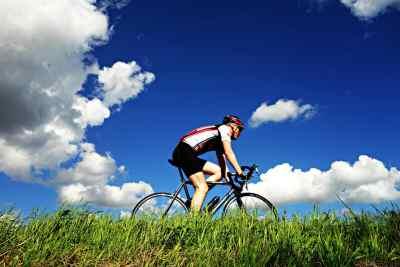 man cycling against beautiful sky