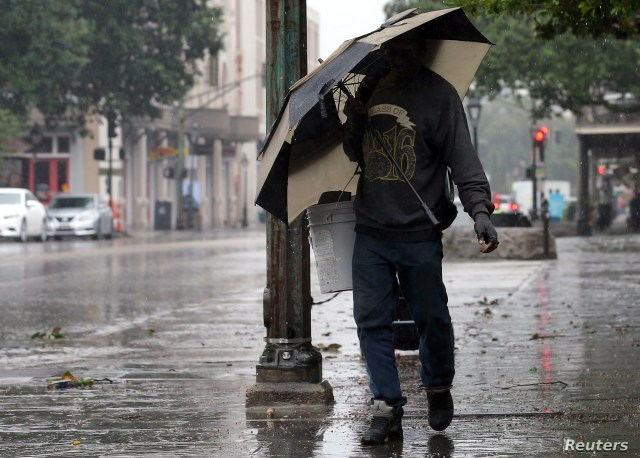 A man walks through rain in the French Quarter caused by Hurricane Barry in New Orleans, July 13, 2019.