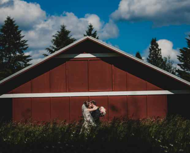 Outdoor wedding photography of a bride and groom posing in front of a red barn on a farm.
