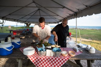 Zach Ripka and Chris Tuturro prepare apetizers and sides for the clambake on Sheffield Island, in Norwalk, Conn. on June 30, 2016.