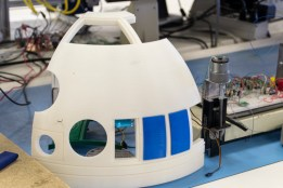 One section of the 3d printed R2D2 dome sits on the work bench. The Dome is being fitted with motors and sensors.