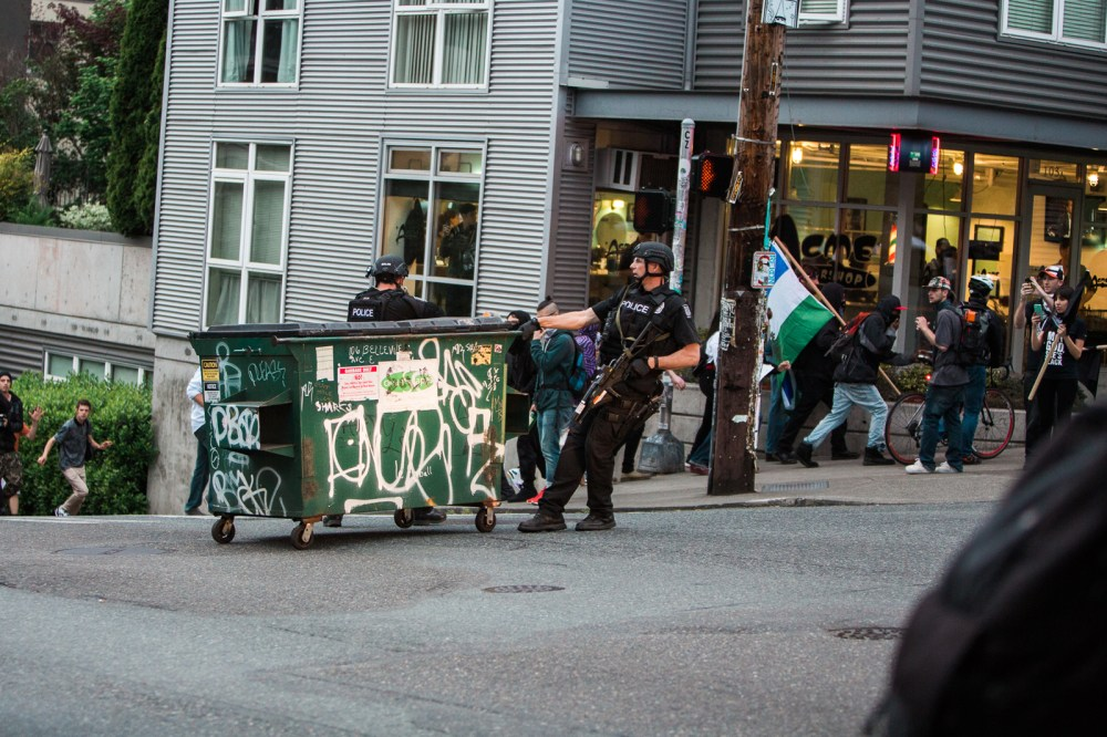 officer keeps a dumpster from rolling