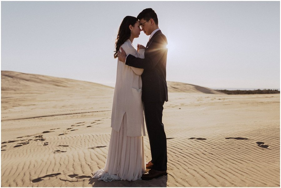 desert inspired elopement couple holding one another silver lake sand dunes michigan