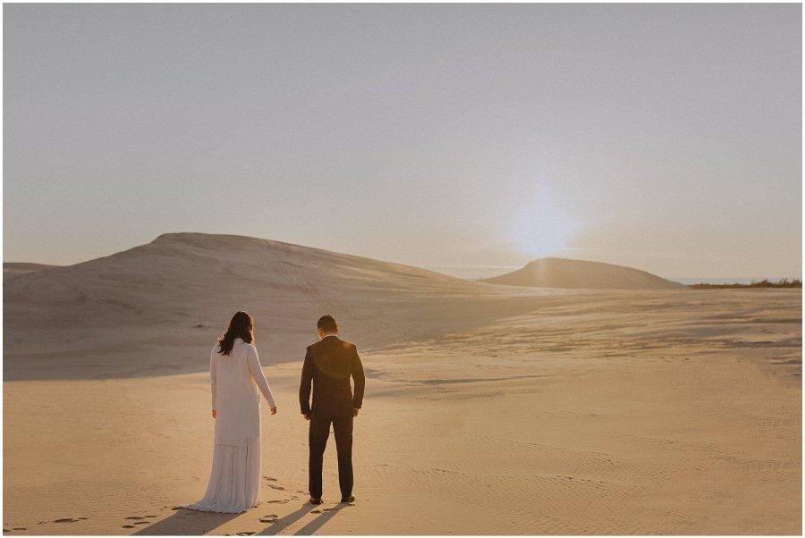 sun setting behind sand dunes