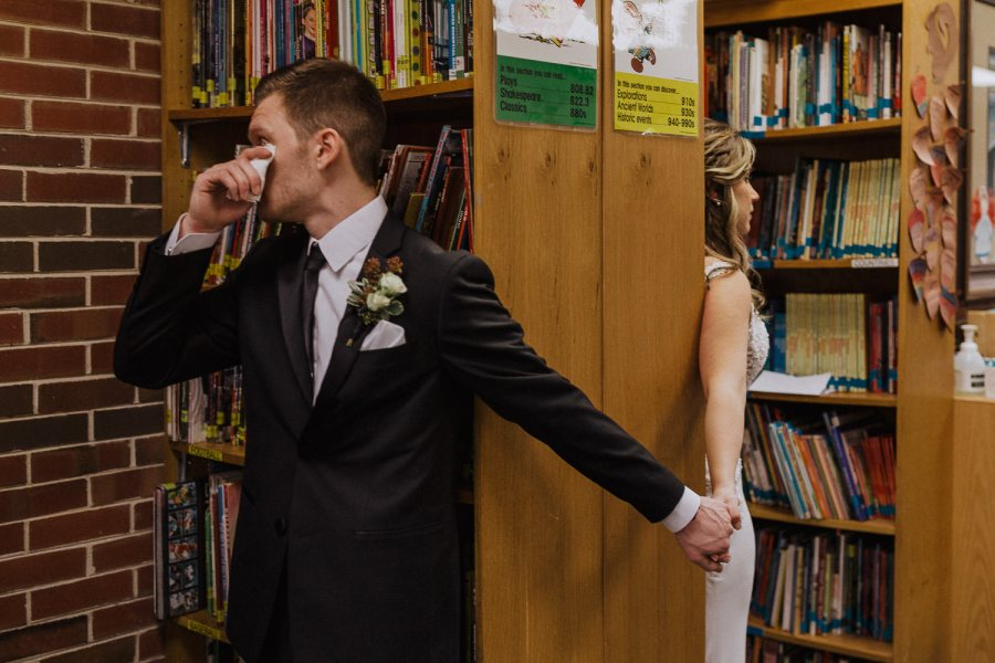 Groom wiping his eyes as he holds his bride's hand around a bookshelf