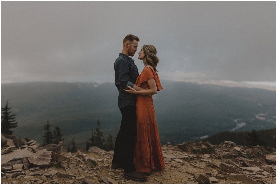 couple standing looking at one another on top of a mountain