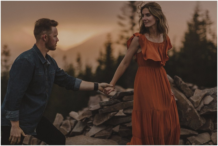 a couple walking on a mountain while the sun sets behind them