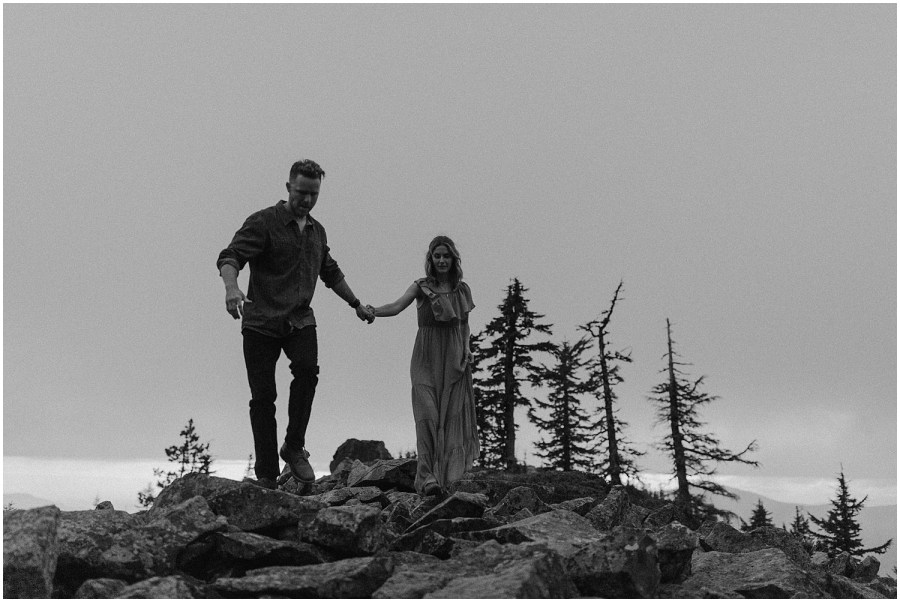 a couple holding hands as they walk down a mountain