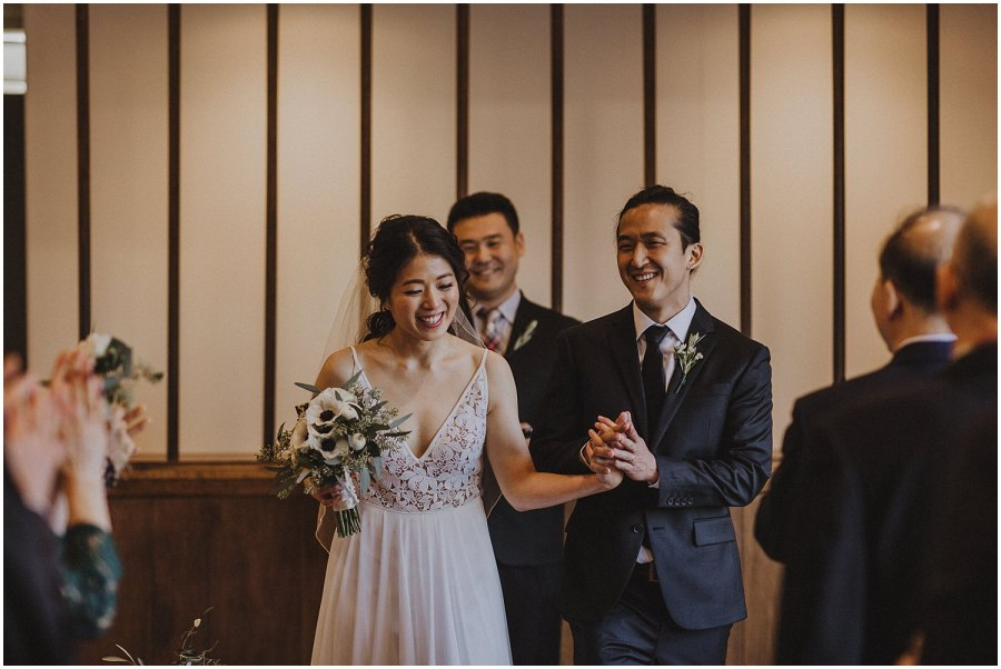 bride and groom walking down the aisle smiling Chicago wedding photographer kyle szeto