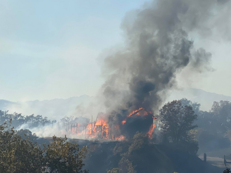 A home burning in the Black Oak Estates as the Hopkins Fire continues to spread. [Photo by Matt LaFever]