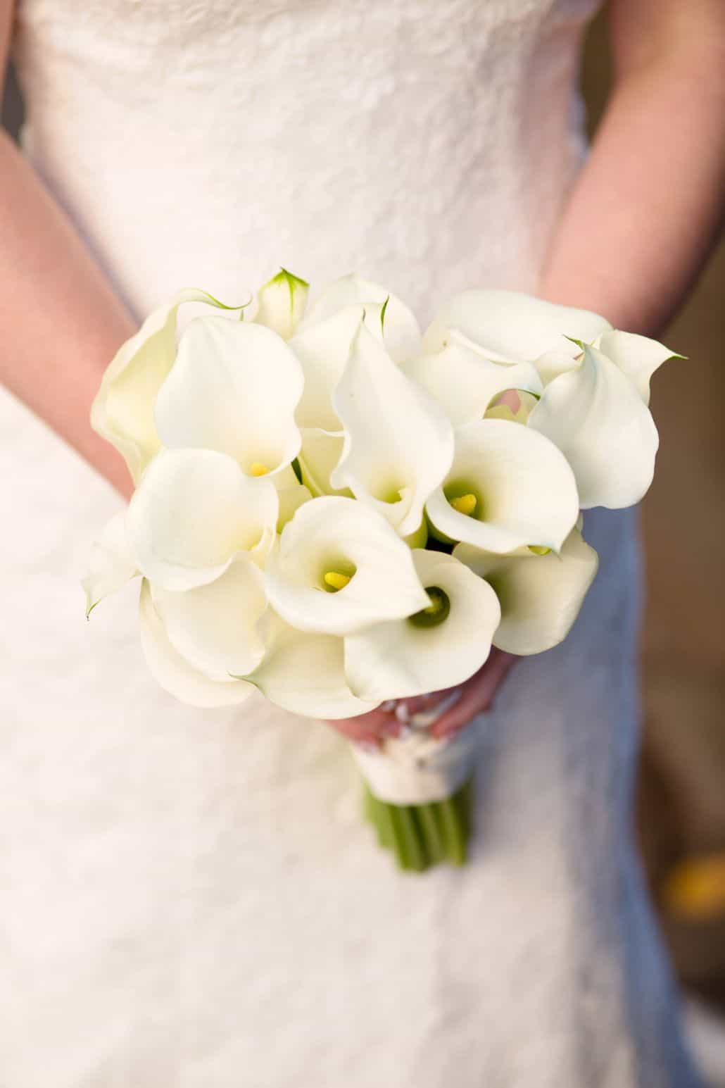 White Calla Lily Bridal Bouquet Held By Bride In Lace Gown