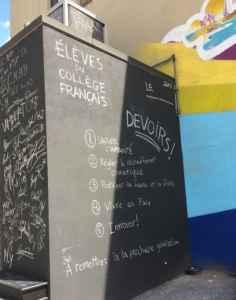 Un tableau noir rappelle aux élèves leurs devoirs.