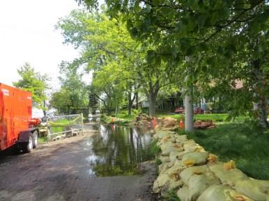 L'eau envahit le trottoir du petit village de l'île Ward, protégé par des sacs de sable. (Photo: Martine Rheault)