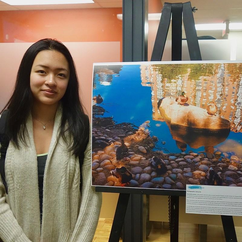 """Jenny Ho pose à côté de sa photographie """"La mare aux canards"""""""