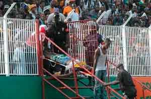 Un hombre saca en camilla a un aficionado lesionado. AP
