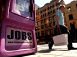 A pedestrian walks by a vending box for a job listing newspaper in New York City. (AFP)