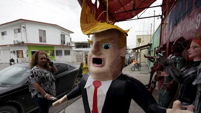 A Mexican client who lives in the U.S., looks at a pinata depicting U.S. Republican presidential candidate Donald Trump hanging outside a workshop in Reynosa