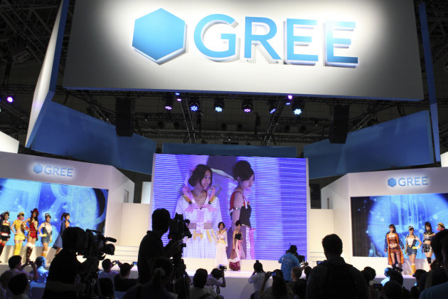 Staff members promote at a booth for social networking service Gree Inc. at the Tokyo Game Show in Chiba, east of Tokyo, Thursday, Sept. 15, 2011. A startup little known outside Japan that offers game